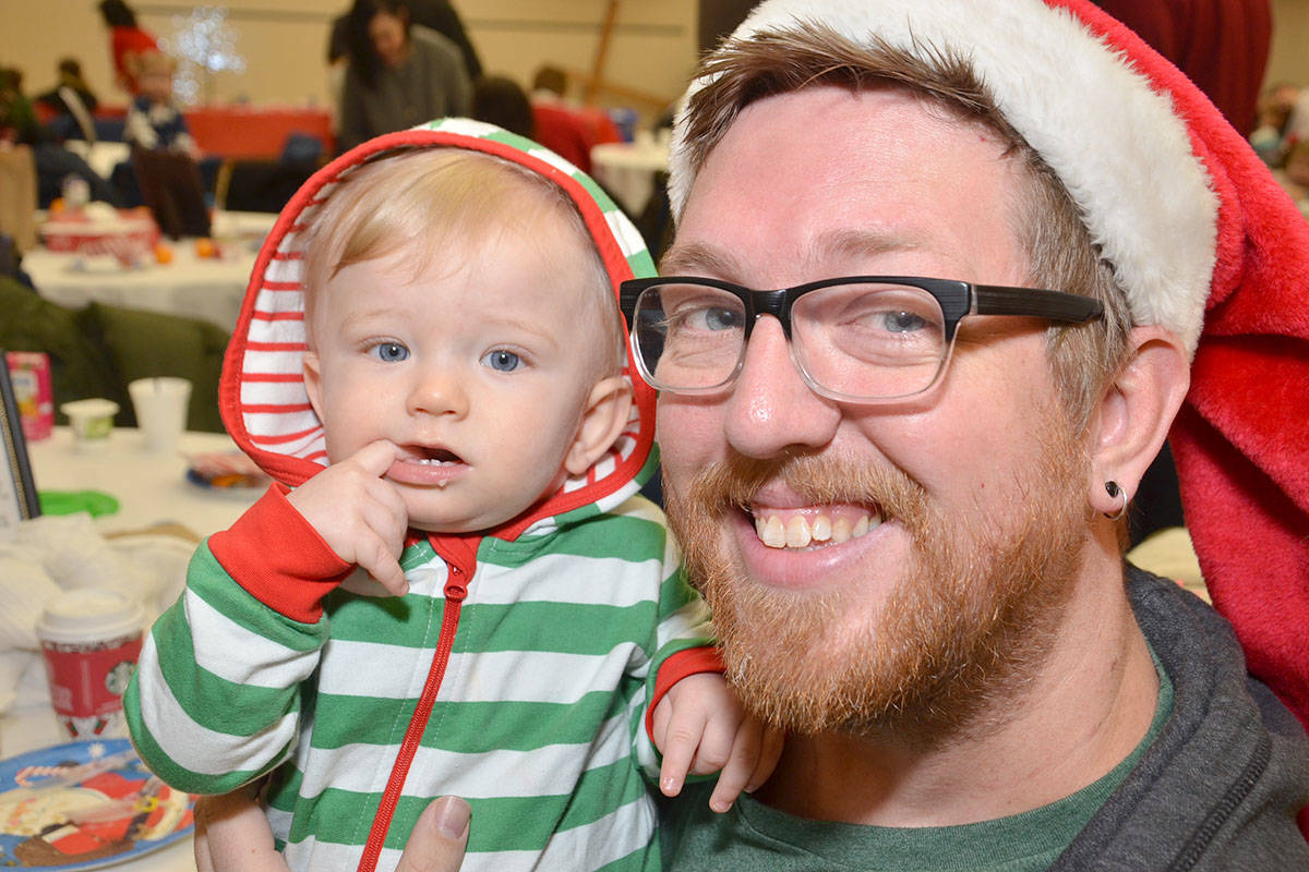 Felix turns one in mid-December and in his elfen onesie was all gussied up for breakfast with dad, Ty Petkau. They were among the many at the R.C. Garnett Demonstration School for the Santa Breakfast hosted by the Willows Church on Saturday. (Heather Colpitts/Langley Advance)