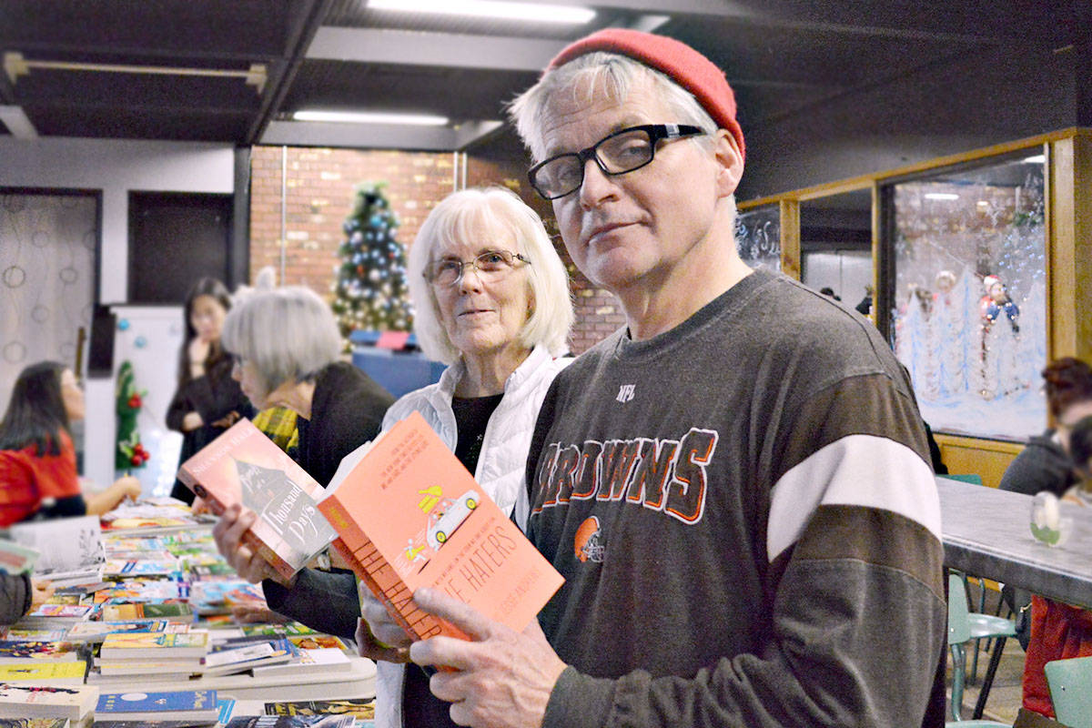 Wilma Birkett and Mike McLeod volunteered with Wrap-a-Read, the program of the Langley Literacy Association that provides a new book for each child helped by the Langley Christmas Bureau. (Bailey Martens/Special to the Langley Advance)