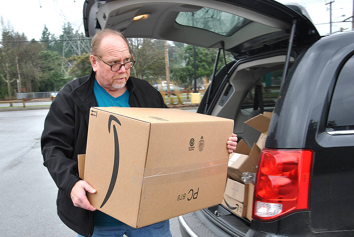 Tom Cook of Surrey dropped off clothing and a box of jackets to Cierra Foster Saturday in Brookswood, during her donation drive at the George Preston Recreation Centre. (Roxanne Hooper/Langley Advance)