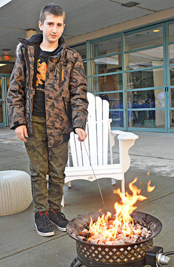 Fire pits were outside at the Walnut Grove Gator Xmas Extravaganza on Dec. 22 to allow students such as Kai Damgajjan to roast marshmallows and hot dogs. (Bailey Martens/Special to the Langley Advance)
