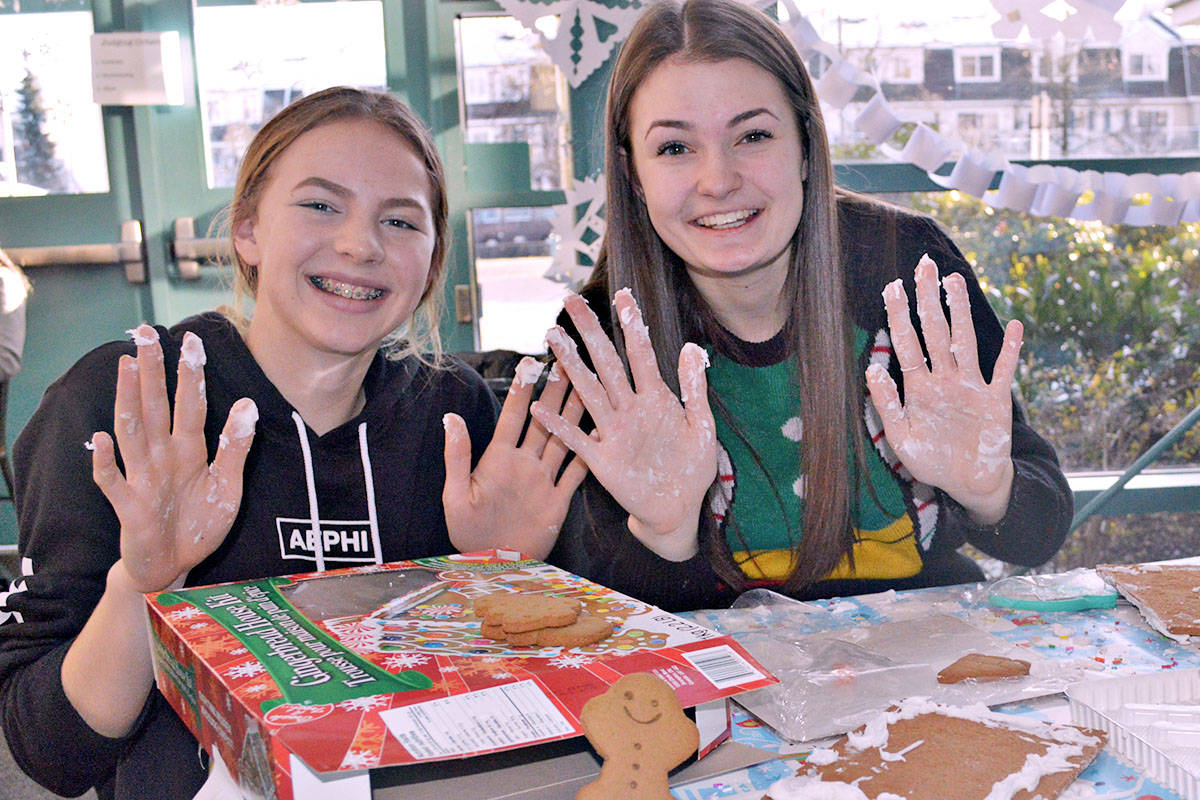Holly Harrison and Katie LaFace found out gingerbread house decorating was a messy task at Walnut Grove Secondary. (Bailey Martens/Special to the Langley Advance)