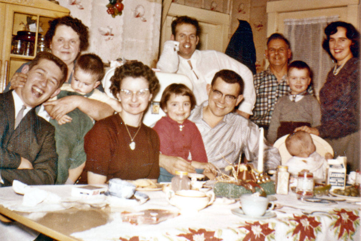 Members of the DesRochers family assembled around a table in a house. Milly DesRochers is standing in the back on the left, Ramon DesRochers is standing in the back in a white shirt, and Lorraine DesRochers is on the far right. The man in front of the door might be Wilfred DesRochers, and the young boys on the left and right appear to be Randy and Wayne. (Langley Centennial Museum)