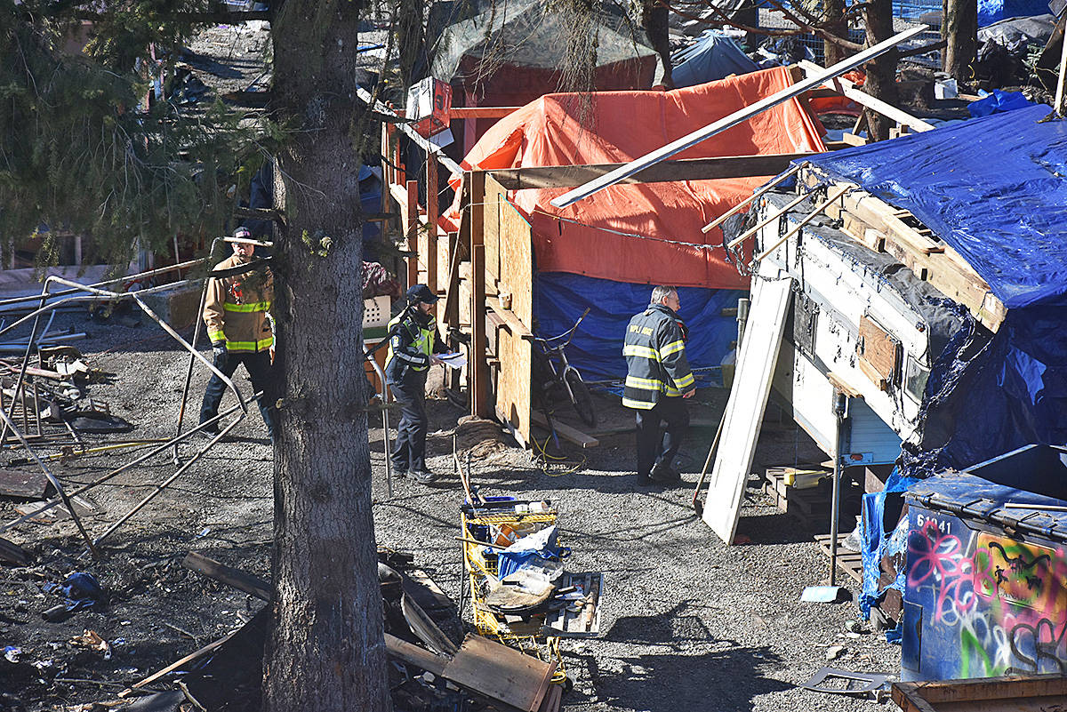 Firefighters inspect the camp on Saturday afternoon. (Neil Corbett/THE NEWS)