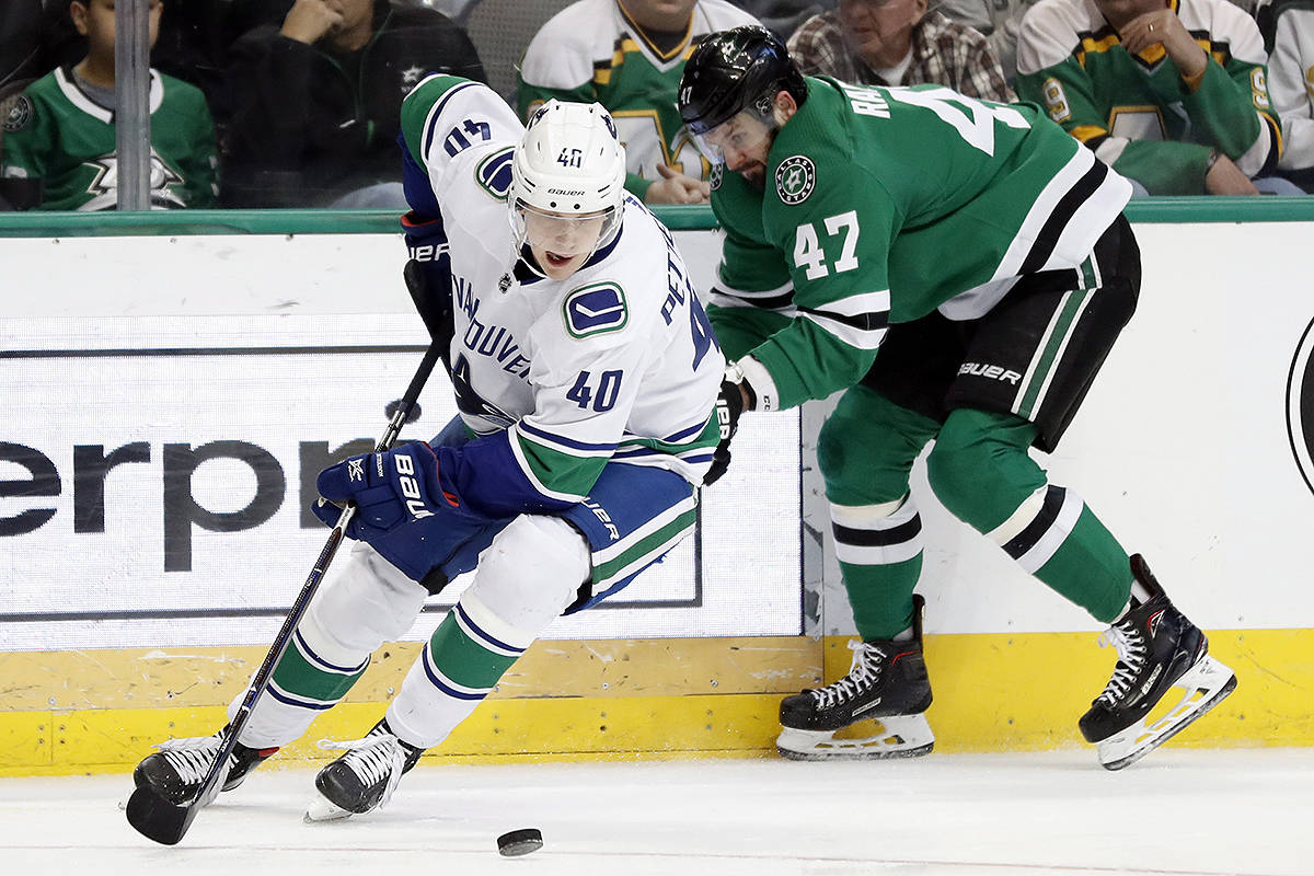 Vancouver Canucks centre Elias Pettersson (40) skates away with control of the puck in front of Dallas Stars right wing Alexander Radulov (47) in the first period of an NHL hockey game in Dallas, Sunday, March 17, 2019. (AP Photo/Tony Gutierrez)