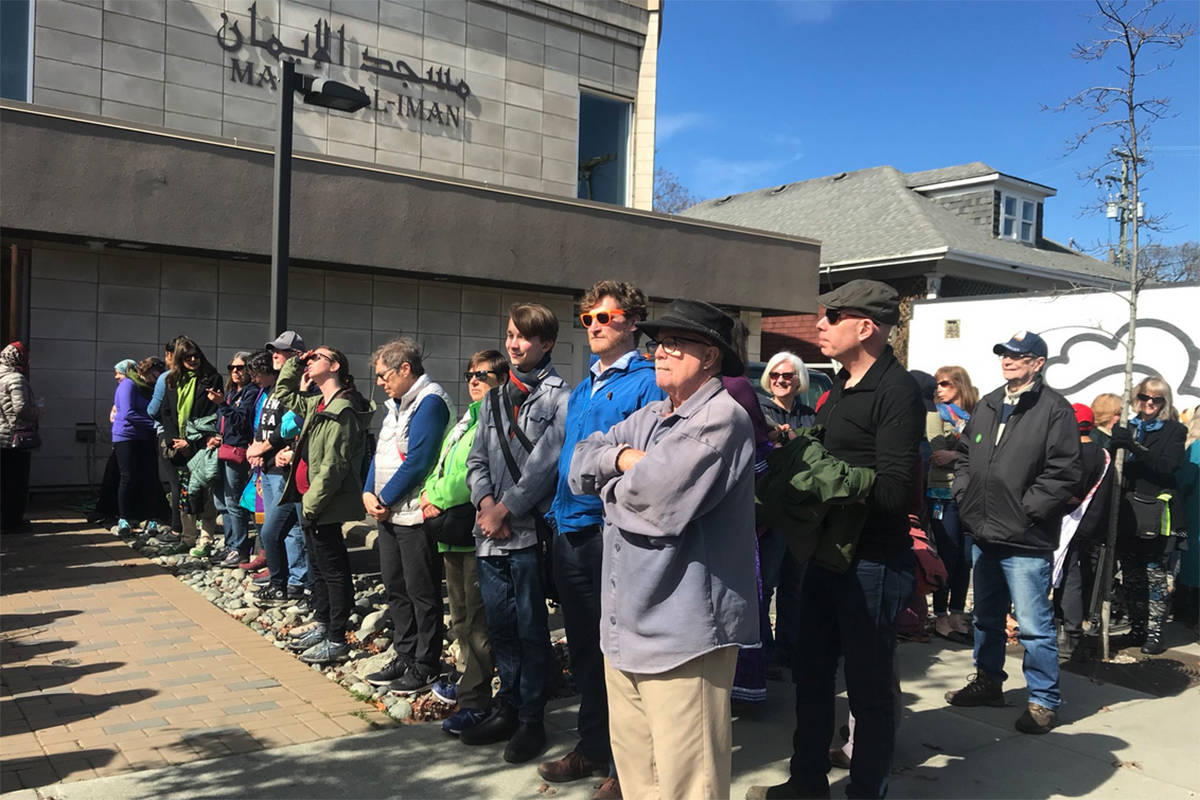 A human chain around Victoria's Masjid Al-Iman mosque – a show of support for the Muslim community inside holding Friday prayer. (Keri Coles/News Staff)