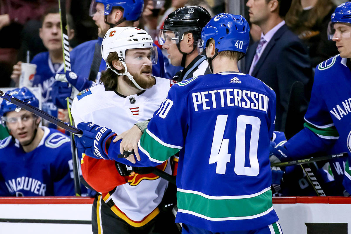 Calgary Flames' Rasmus Andersson (4) holds Vancouver Canucks' Elias Pettersson (40) during second period NHL hockey action in Vancouver on Saturday, March 23, 2019. THE CANADIAN PRESS/Ben Nelms