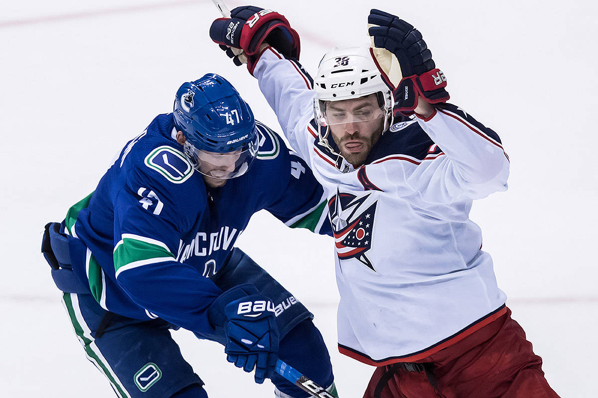 Vancouver Canucks' Sven Baertschi, left, of Switzerland, checks Columbus Blue Jackets' Boone Jenner during the second period of an NHL hockey game in Vancouver, on Sunday March 24, 2019. THE CANADIAN PRESS/Darryl Dyck
