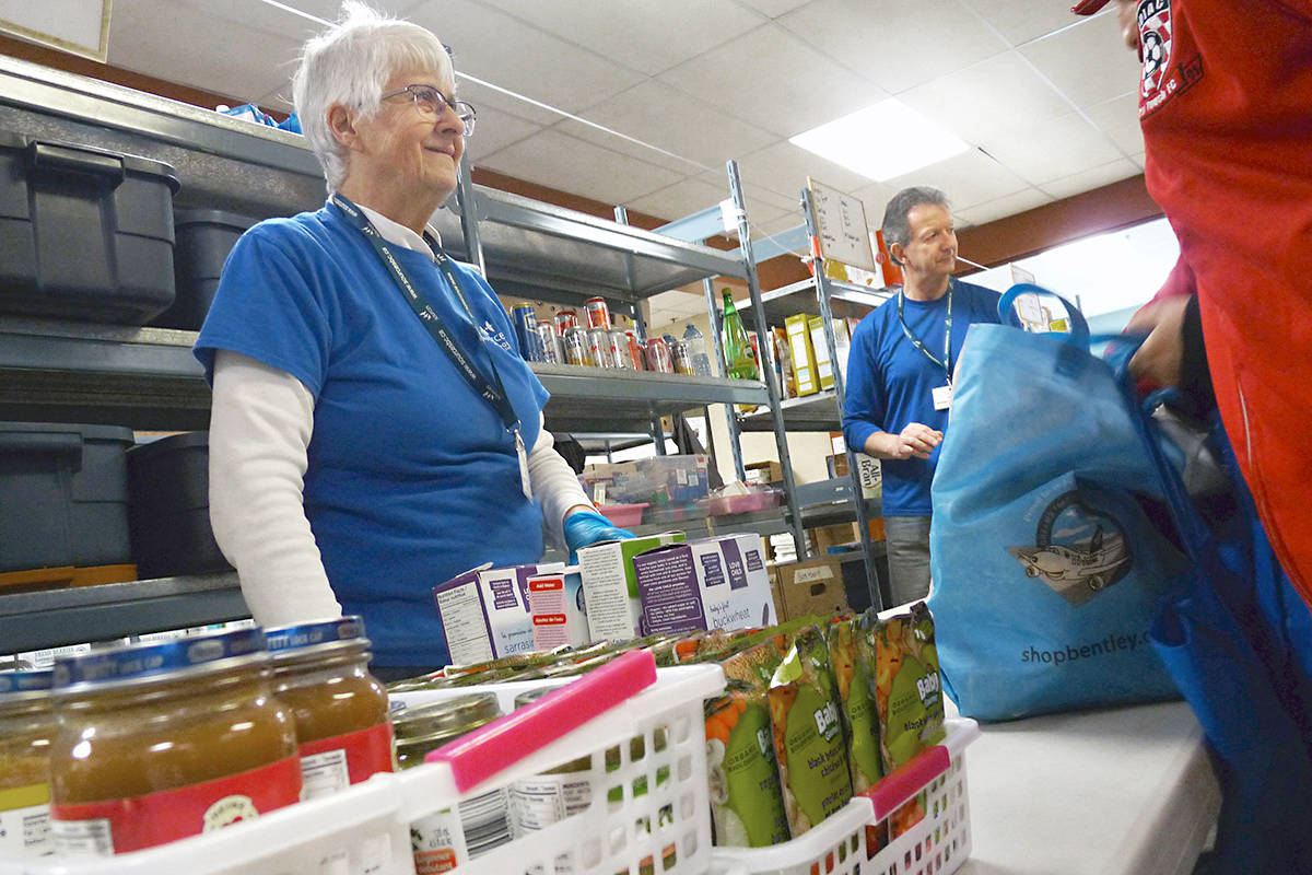 Volunteers Gail Epp and Harry Marsland fill bags at the regular Wednesday distribution by the Sources Langley Food Bank. Clients were delighted to hear the food bank has found a new home. Dan Ferguson Langley Advance Times