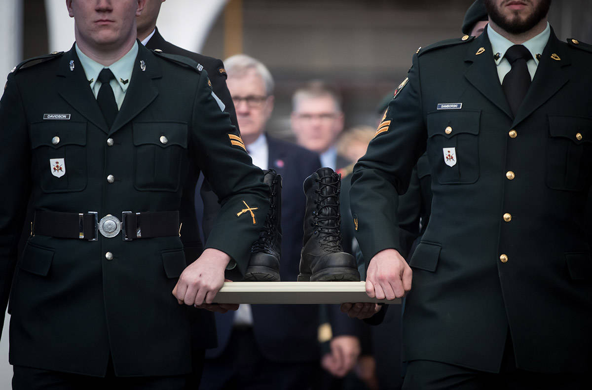 Members of the Canadian Forces carry a pair of combat boots to a VIA Rail train to begin their journey to Halifax, at Pacific Central Station in Vancouver, on Friday March 29, 2019. The boots will travel across the country on the train to symbolize those who travelled to Halifax during the Second World War before they embarked for Europe. The journey is part of the federal government's plan to commemorate the 7th anniversary of D-Day and the Battle of Normandy. (Darryl Dyck/The Canadian Press)