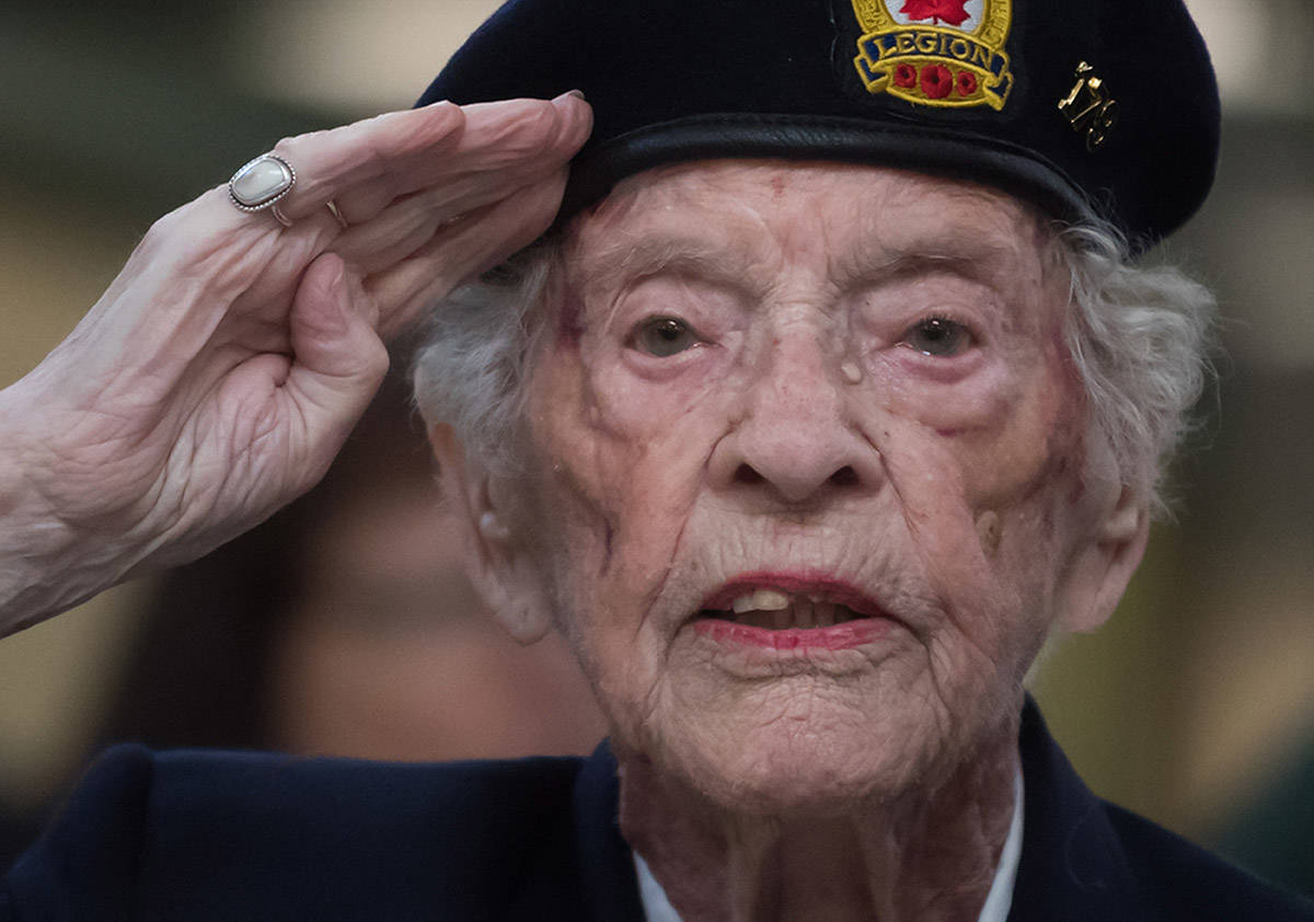 Agnes Keegan, who served in the British Army during the Second World War and now lives in Canada, salutes while singing the national anthem during a departure ceremony for a pair of combat boots that will travel to Halifax on a VIA Rail train, at Pacific Central Station in Vancouver, on Friday March 29, 2019. The boots will travel across the country on the train to symbolize those who travelled to Halifax during the Second World War before they embarked for Europe. The journey is part of the federal government's plan to commemorate the 7th anniversary of D-Day and the Battle of Normandy. (Darryl Dyck/The Canadian Press)