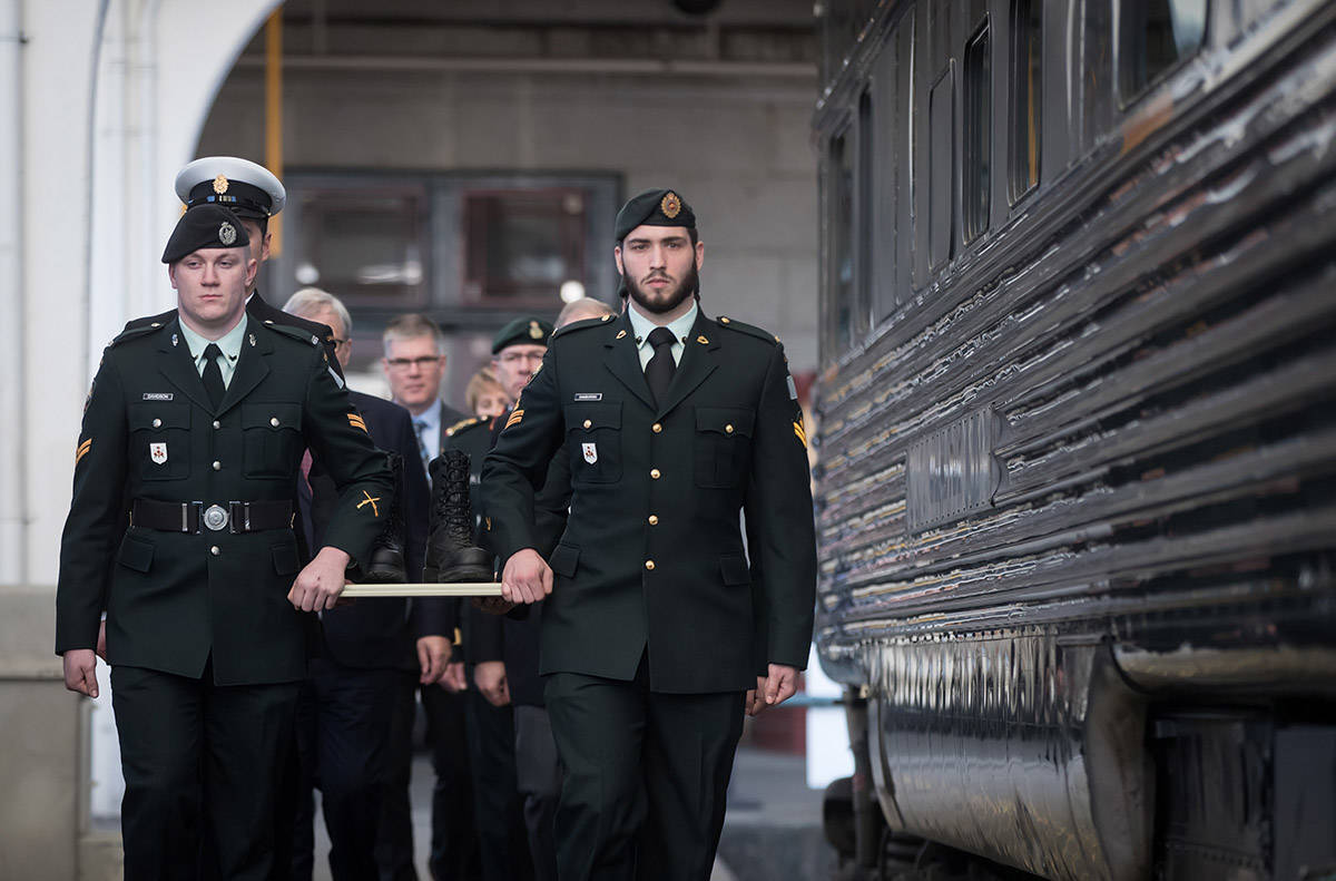 Members of the Canadian Forces carry a pair of combat boots to a VIA Rail train to begin their journey to Halifax, at Pacific Central Station in Vancouver, on Friday March 29, 2019. The boots will travel across the country on the train to symbolize those who travelled to Halifax during the Second World War before they embarked for Europe. The journey is part of the federal government's plan to commemorate the 75th anniversary of D-Day and the Battle of Normandy. (Darryl Dyck/The Canadian Press)