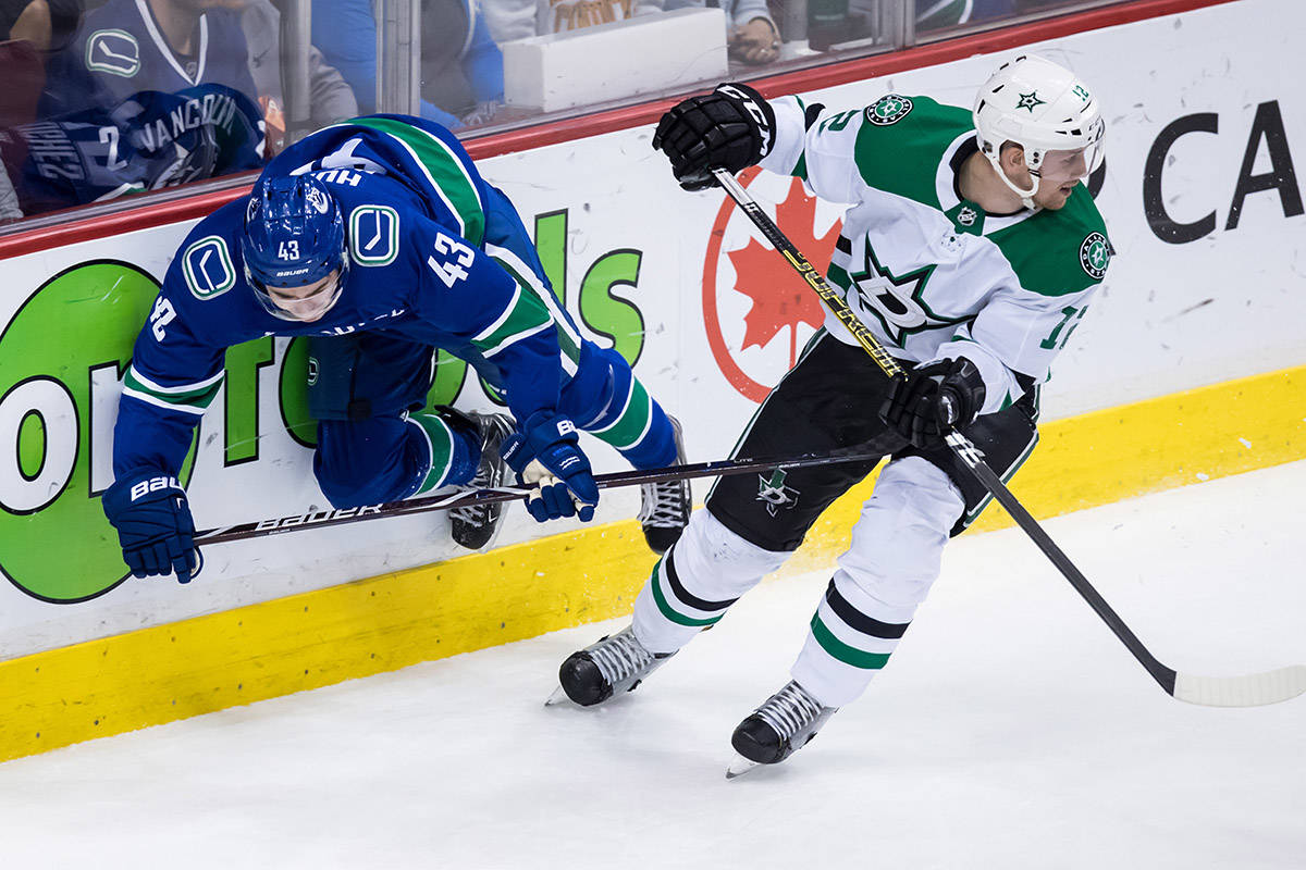 Dallas Stars' Radek Faksa, right, of the Czech Republic, checks Vancouver Canucks' Quinn Hughes during the second period of an NHL hockey game in Vancouver, on Saturday March 30, 2019. THE CANADIAN PRESS/Darryl Dyck