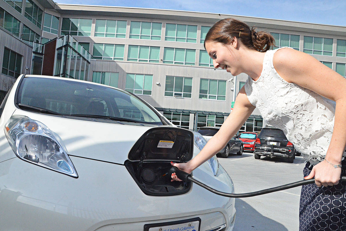 Tanya Drouillard of the Township of Langley plugs in a Nissan Leaf, one of two all-electric vehicles operated by the Township, a public charging station. (Matthew Claxton/Langley Advance Times)