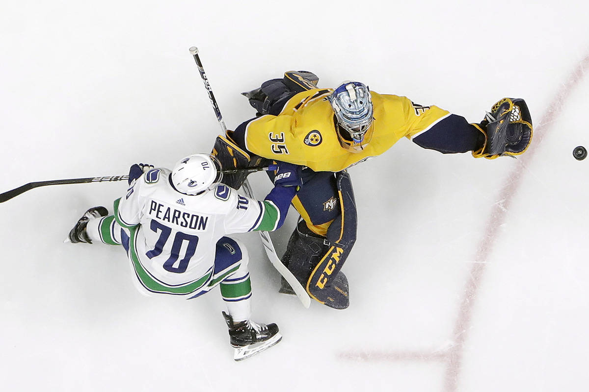Nashville Predators goaltender Pekka Rinne (35), of Finland, comes away from the net to grab the puck as Vancouver Canucks left wing Tanner Pearson (70) closes in during the second period of an NHL hockey game Thursday, April 4, 2019, in Nashville, Tenn. (AP Photo/Mark Humphrey)