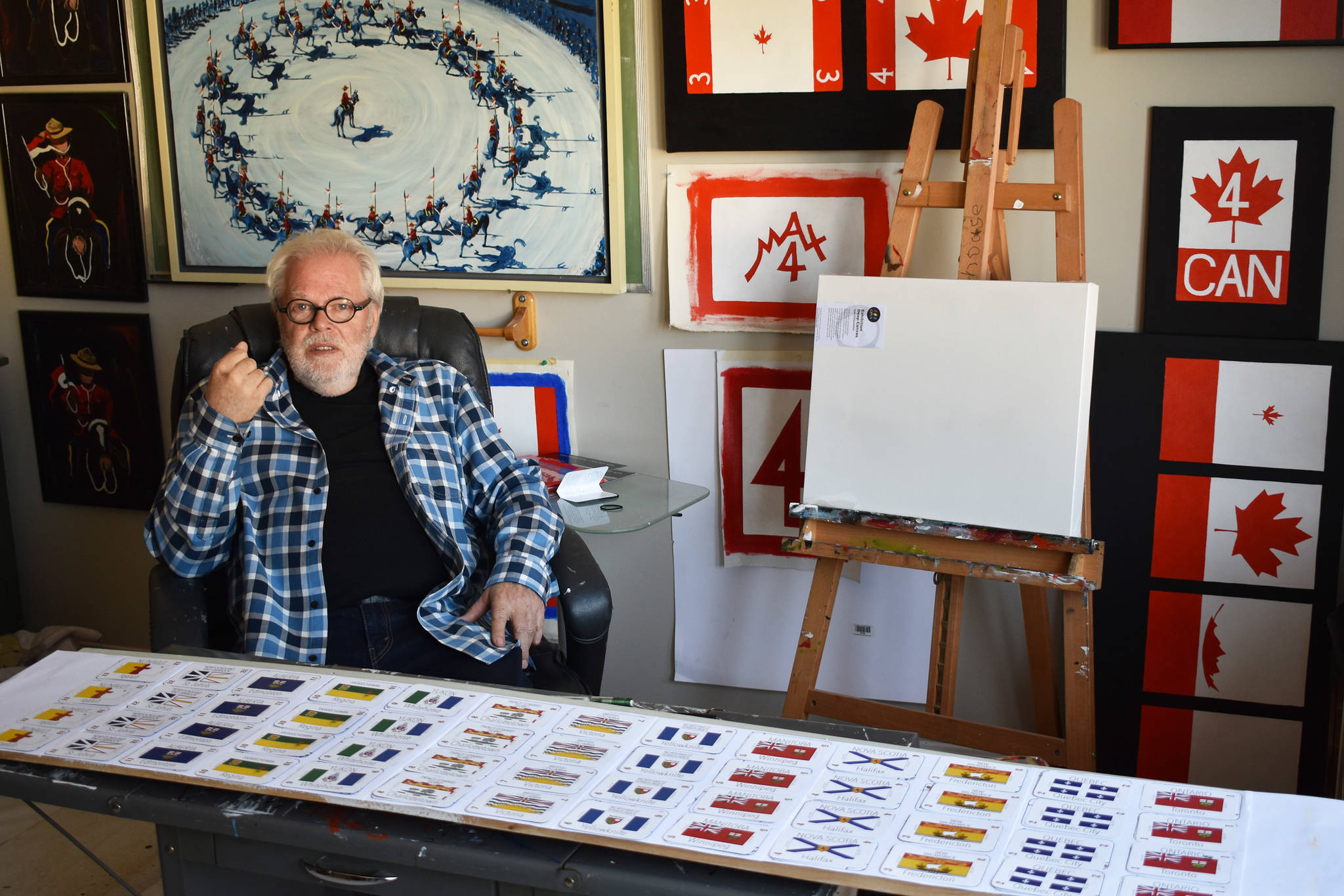 Max Newhouse in his studio. Cards for his Canadian game are laid out in front of him, while images of the Canadian flag and the RCMP musical ride hang on the wall behind him. (Grace Kennedy/The Observer)