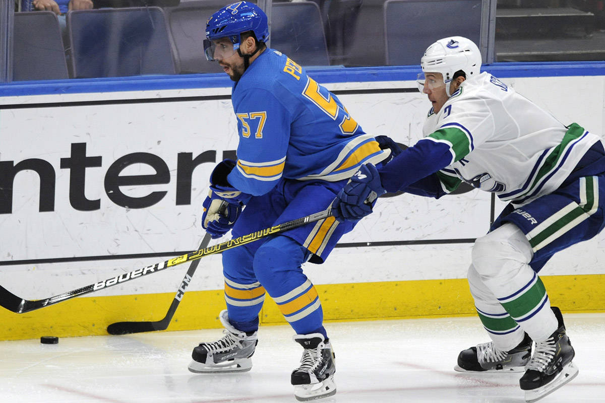 St. Louis Blues' David Perron (57) reaches for the puck against Vancouver Canucks' Luke Schenn (2) during the second period of an NHL hockey game, Saturday, April 6, 2019, in St. Louis. (AP Photo/Bill Boyce)