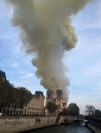 Notre Dame cathedral is burning in Paris, Monday, April 15, 2019. Massive plumes of yellow brown smoke is filling the air above Notre Dame Cathedral and ash is falling on tourists and others around the island that marks the center of Paris. (AP Photo/Lori Hinant)                                Notre Dame cathedral is burning in Paris, Monday, April 15, 2019. Massive plumes of yellow brown smoke is filling the air above Notre Dame Cathedral and ash is falling on tourists and others around the island that marks the center of Paris. (AP Photo/Lori Hinant)