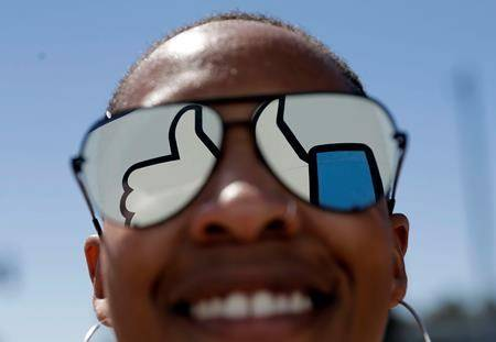 In this March 28, 2018, file photo, a visitor poses for a photo with the Facebook logo reflected on her sunglasses at the company's headquarters in Menlo Park, Calif. (AP Photo/Marcio Jose Sanchez, File)