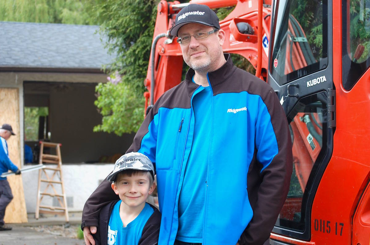 Cayden Berden and his dad Daryl came during a day off of school to help out during demolition day at the Aldergrove home. (Sarah Grochowski photo)