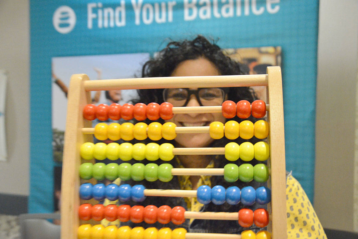 Lauren Johnson used an abacus for her quiz about physical and emotional health at the Find Your Balance booth, presented by BC Responsible and Problem Gambling. It was one of many social service agencies at the expo. (Heather Colpitts/Langley Advance Times)