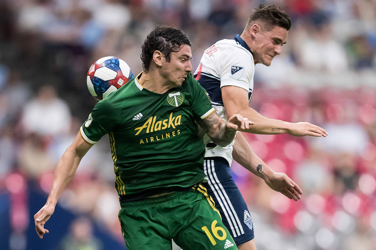 Portland Timbers' Zarek Valentin, front left, and Vancouver Whitecaps' Jake Nerwinski vie for the ball during the second half of an MLS soccer game in Vancouver on Friday May 10, 2019. THE CANADIAN PRESS/Darryl Dyck