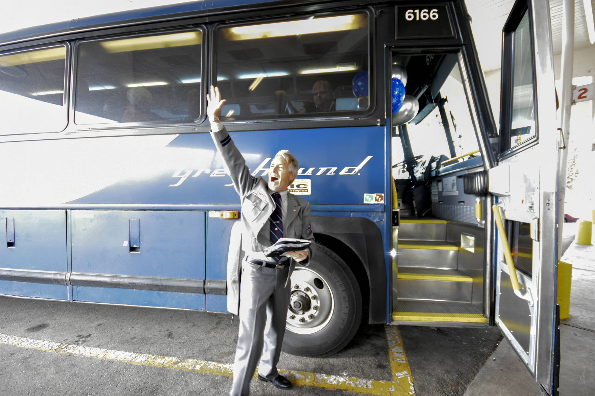Veteran Greyhound bus driver Blake Moore gives a shout out to those who gathered to wish him well on his final route Wednesday. Mark Brett/Western News