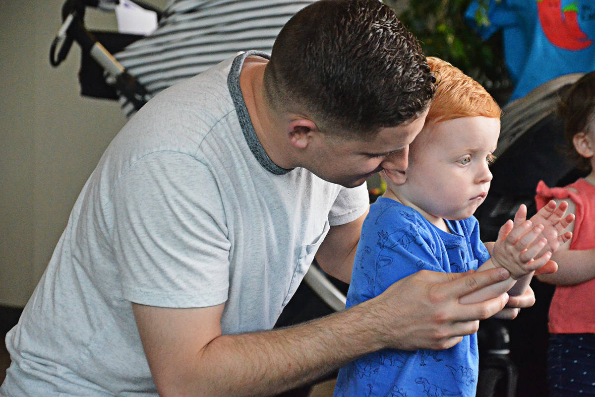 Scott McClure with his 22-month-old son Alastair clapped along with the Springmans band at Langley Child Day Wednesday. (Matthew Claxton/Langley Advance Times)
