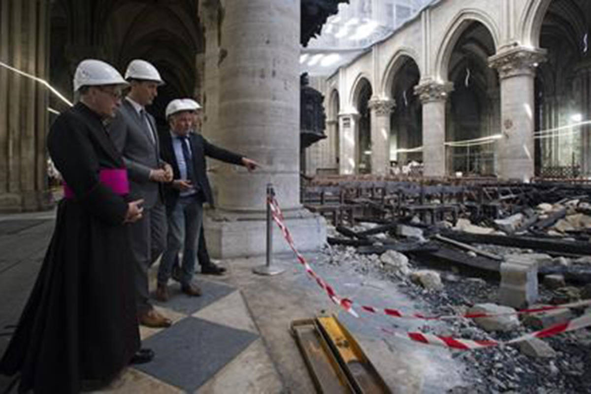 Restoration Project Chief Architect Philippe Villeneuve gives Canadian Prime Minister Justin Trudeau and Rector-Archpriest of the Notre-Dame de Paris Cathedral Patrick Chauvet a tour of the remains of the Notre Dame de Paris Cathedral in Paris, Wednesday, May 15, 2019. THE CANADIAN PRESS/Adrian Wyld