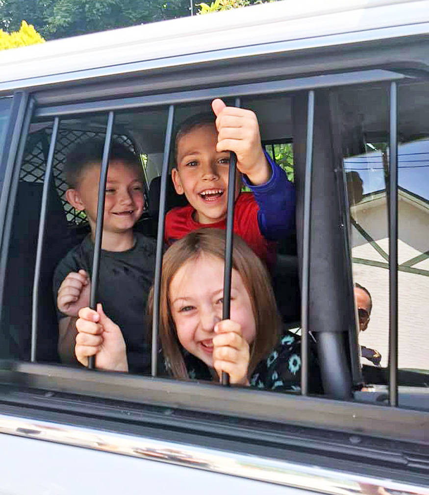 Austin Hall-Waters (middle) his sister Jahnessa LaRocque and his friend Jackson Rhodes (left) pile into the back of a Mission RCMP police cruiser. / FaceBook Photo