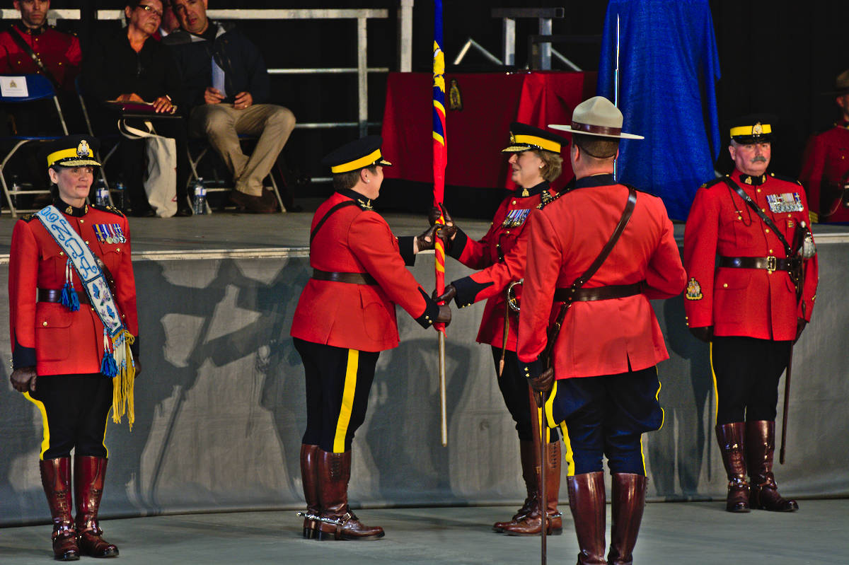 RCMP Commissioner Brenda Lucki hands the divisional ensign to Deputy Commissioner Jennifer Strachan, symbolically handing over the reins of the RCMP's E division from Brenda Butterworth-Carr (left). (Photo: Nick Laba)