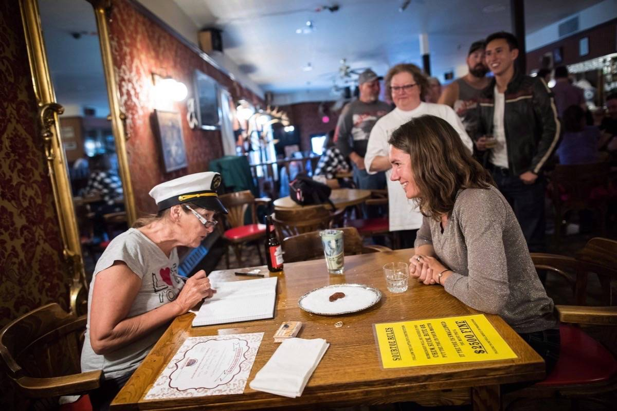 "Celine Gerakin, right, listens to ""Toe Captain"" Sue Taylor before drinking the Sourtoe Cocktail, a drink containing a dehydrated human toe, in Dawson City, Yukon, in 2018. (THE CANADIAN PRESS/Darryl Dyck)"