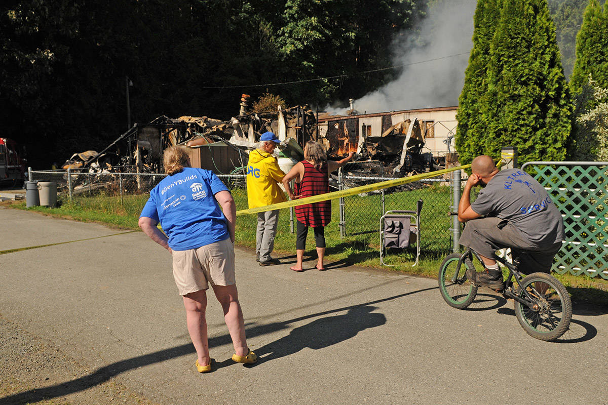 Neighbours watch as firefighters put out a fire in the mobile home next door to one that burned to the ground hours earlier at Cultus Lake Village on Thursday. (Jenna Hauck/The Progress)