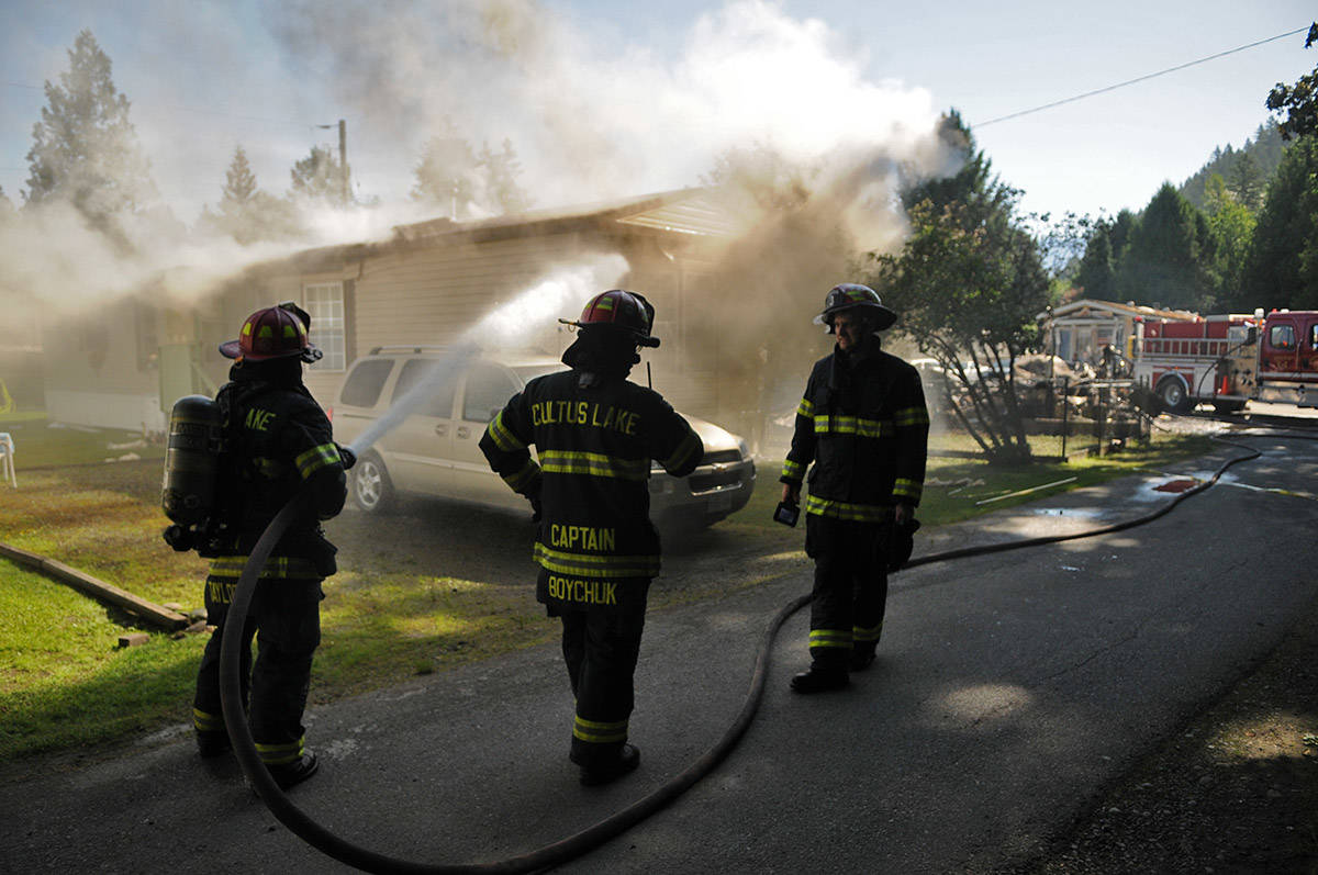 Firefighters extinguish a fire in the mobile home next door to one that burned to the ground hours earlier at Cultus Lake Village on Thursday. (Jenna Hauck/The Progress)