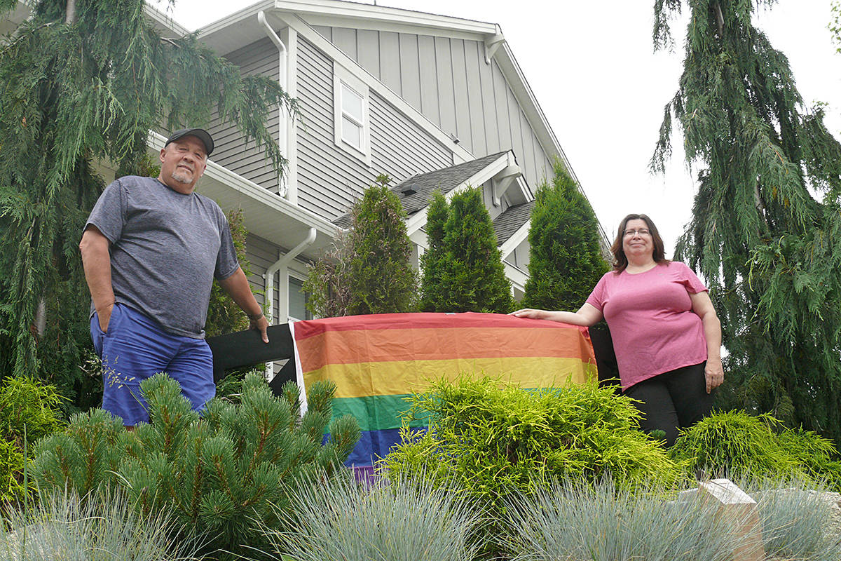 Lisa Ebenal stands with one of her neighbours next to the pride flag in the front yard of her Aldergrove home. After it was mistakenly removed, then returned, by a Township of Langley crew, she said residents of her area began putting up their own flags in a show of support. Dan Ferguson Langley Advance Times