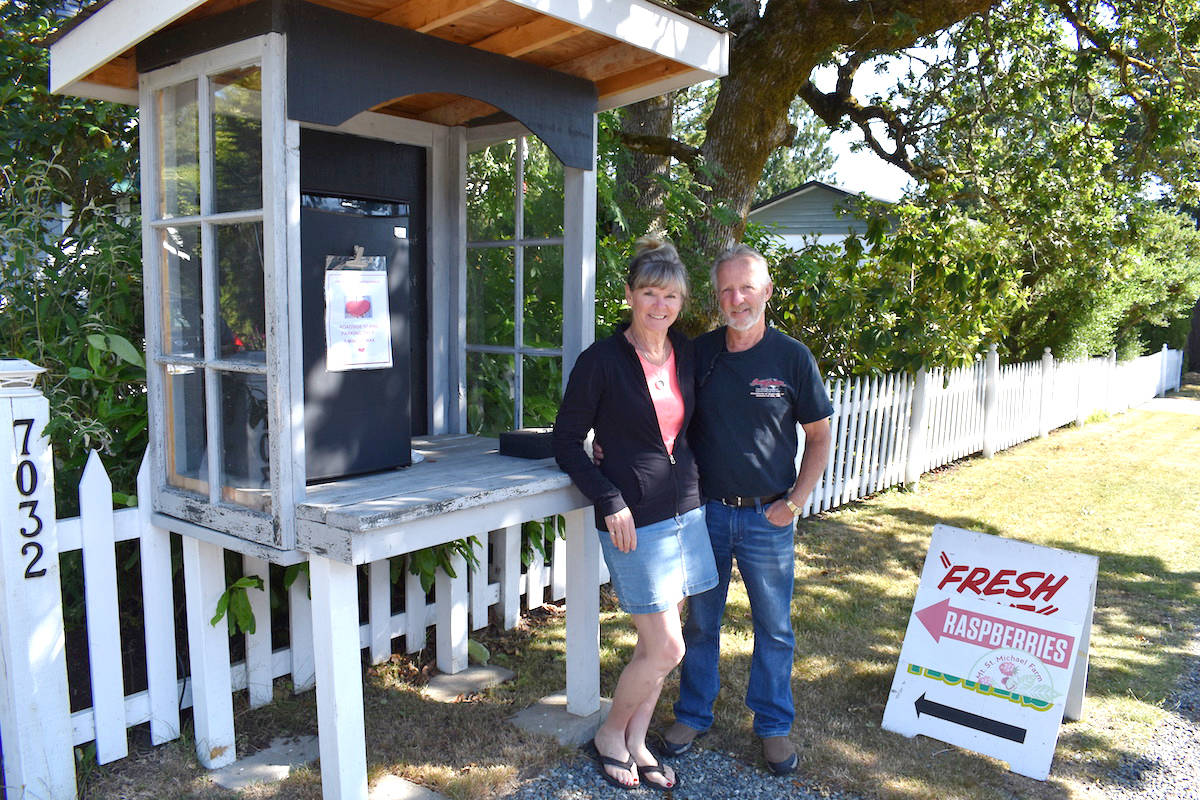Leeanne and Jack Guthrie at the fruit stand outside their Brentwood Bay home. The stand typically sells baskets of raspberries for $5. (Nick Murray/News Staff)