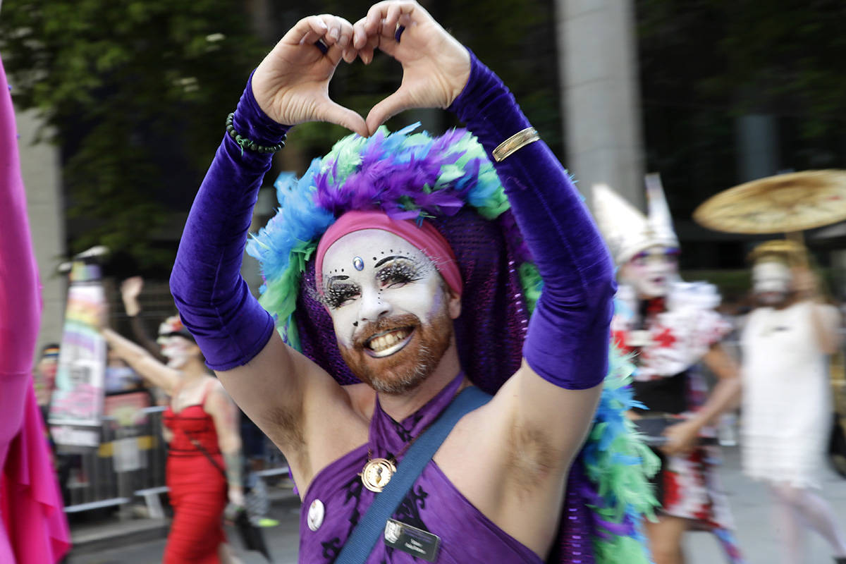 "A member of the Sisters of Perpetual Indulgence makes a ""heart"" symbol toward spectators during the 45th annual Seattle Pride Parade Sunday, June 30, 2019, in Seattle. The parade commemorated both the first ""gay liberation week"" in Seattle in 1974 and the 50th anniversary of the Stonewall uprising, a police raid that sparked the modern-day gay rights movement. (AP Photo/Elaine Thompson)"