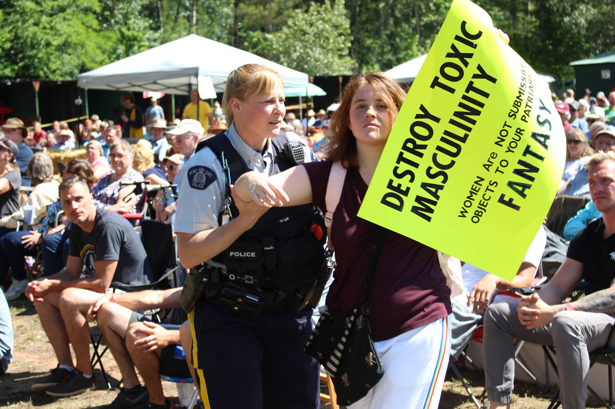 A protester is ushered off to the side at the Mighty Men's Conference in Castlegar on Sunday, June 30, 2019. (John Boivin/Castlegar News)