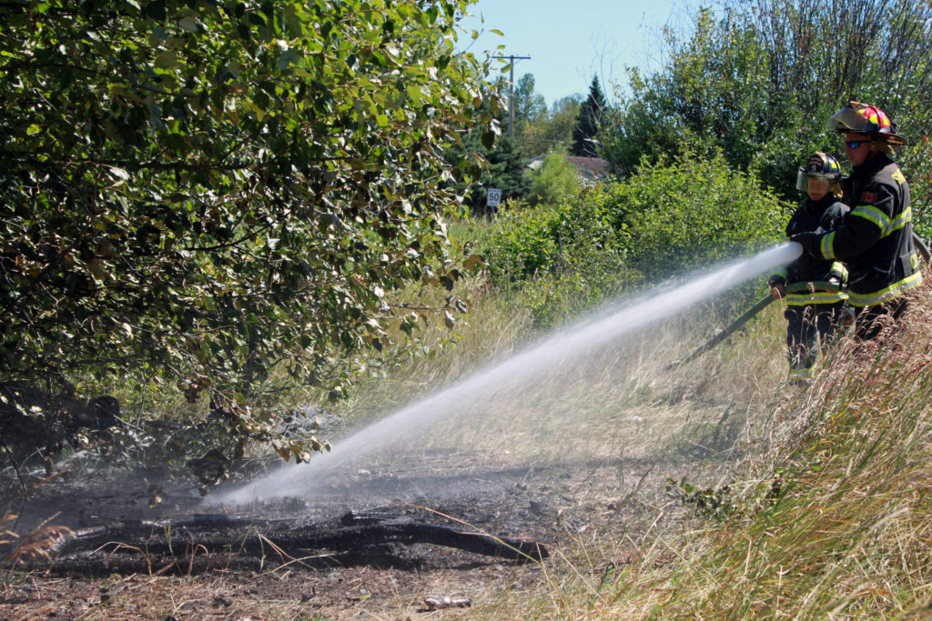 Firefighters extinguish a blaze that started in a wooded area. Township of Langley Fire Department is urging residents to be cautious with materials that have the potential to spark a brush fire. Black Press photo