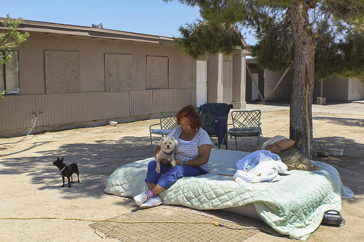 Carmen Morena sits with her dogs on a mattress she pulled out of her home onto the lawn in Ridgecrest, Calif., Saturday, July 6, 2019. Morena says she feels safer sleeping outside than she does inside following the two earthquakes. Officials in California expressed relief Saturday that damage to buildings, roadways and water and gas lines wasn't worse after the largest earthquake the region has seen in nearly 20 years jolted a remote stretch of country from Sacramento to Mexico. But they were also bracing for aftershocks predicted to go on for months. (Maureen Strode/The Bakersfield Californian via AP)