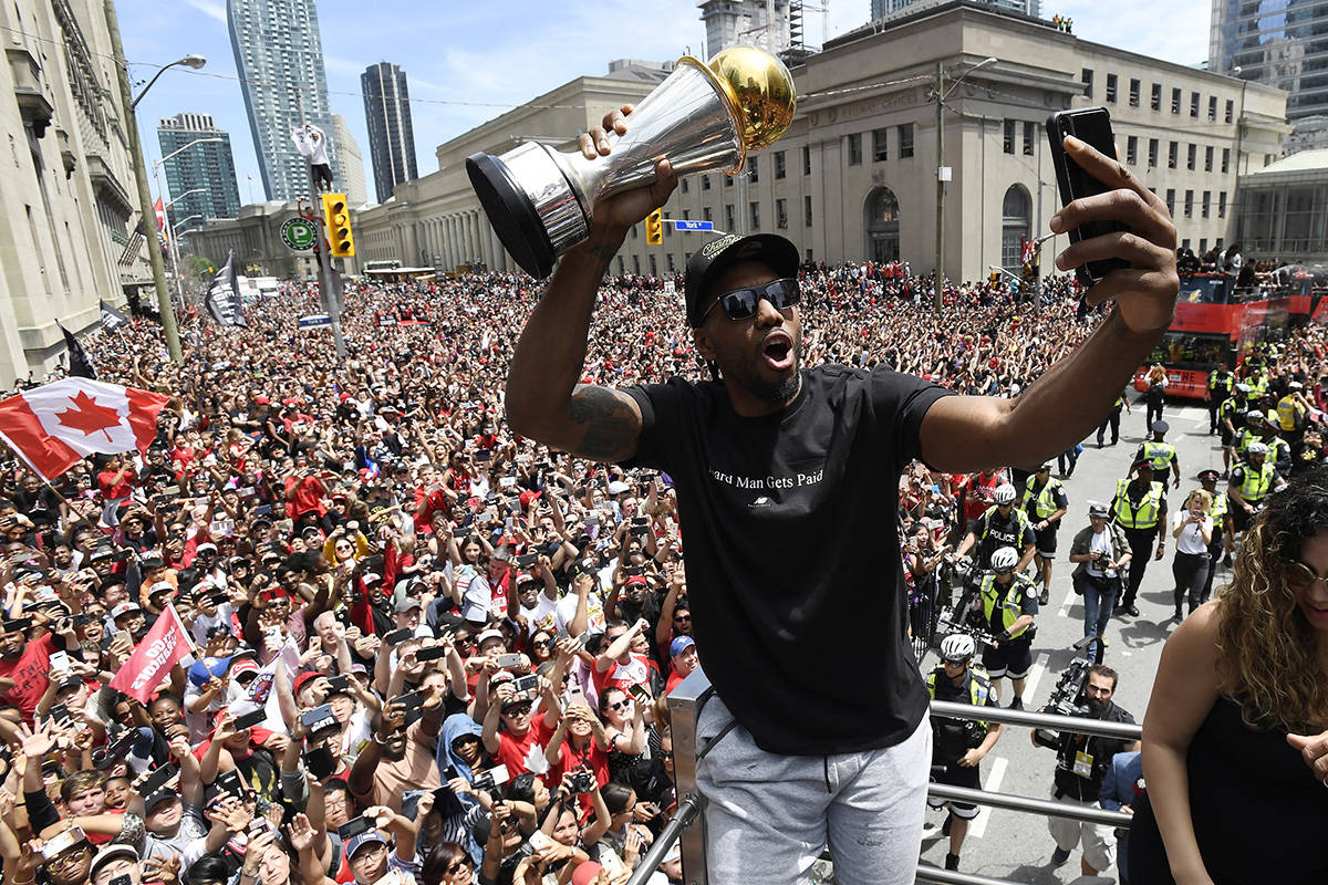 Toronto Raptors forward Kawhi Leonard takes a selfie holding his playoffs MVP trophy during the NBA basketball championship team's victory parade in Toronto, Monday, June 17, 2019. (Frank Gunn/The Canadian Press via AP)