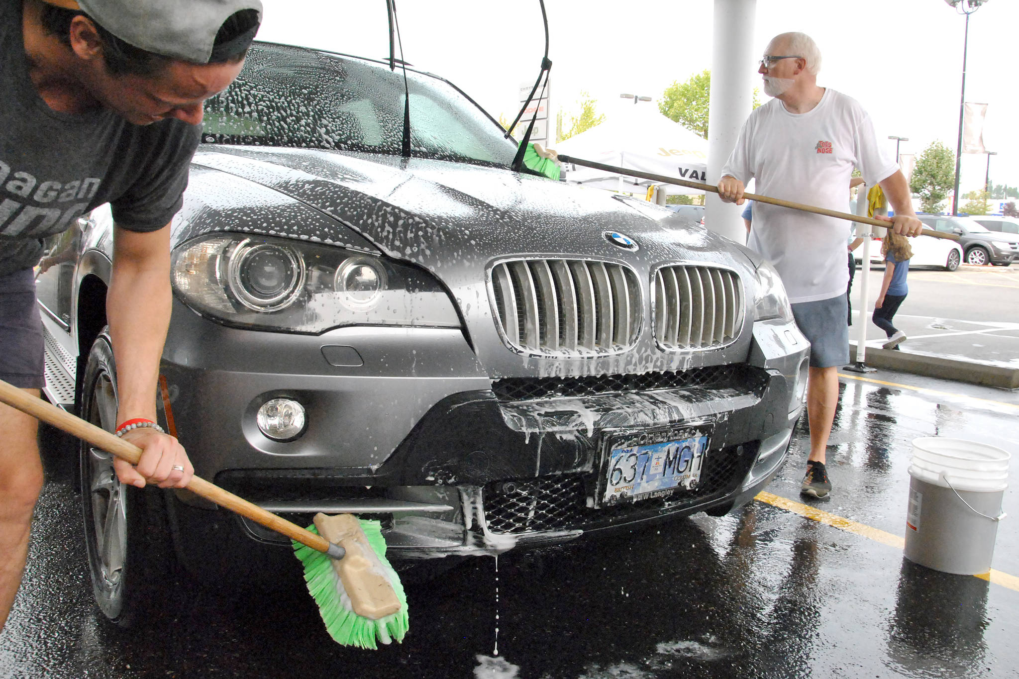 Volunteers scrubbed cars at last year's charity car wash for the Vancouver Cancer Drivers Society. The next car wash is coming up later this month. (Langley Advance Times files)