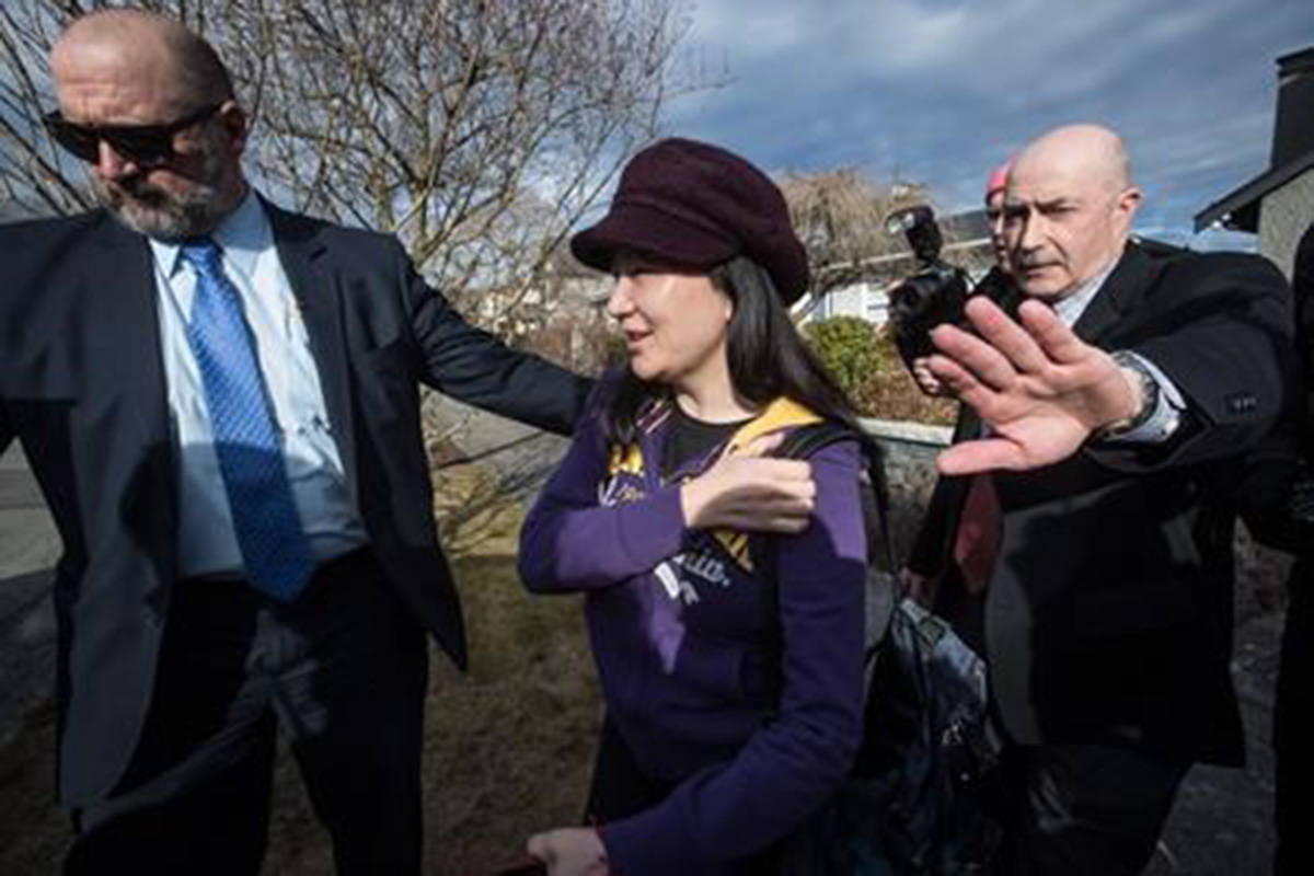 Huawei chief financial officer Meng Wanzhou, centre, is accompanied by a private security detail as she leaves her home to attend a court appearance in Vancouver, on Wednesday March 6, 2019. China's foreign ministry says the recent detention of a Canadian citizen by Chinese authorities is linked to drug allegations against foreign students. THE CANADIAN PRESS/Darryl Dyck