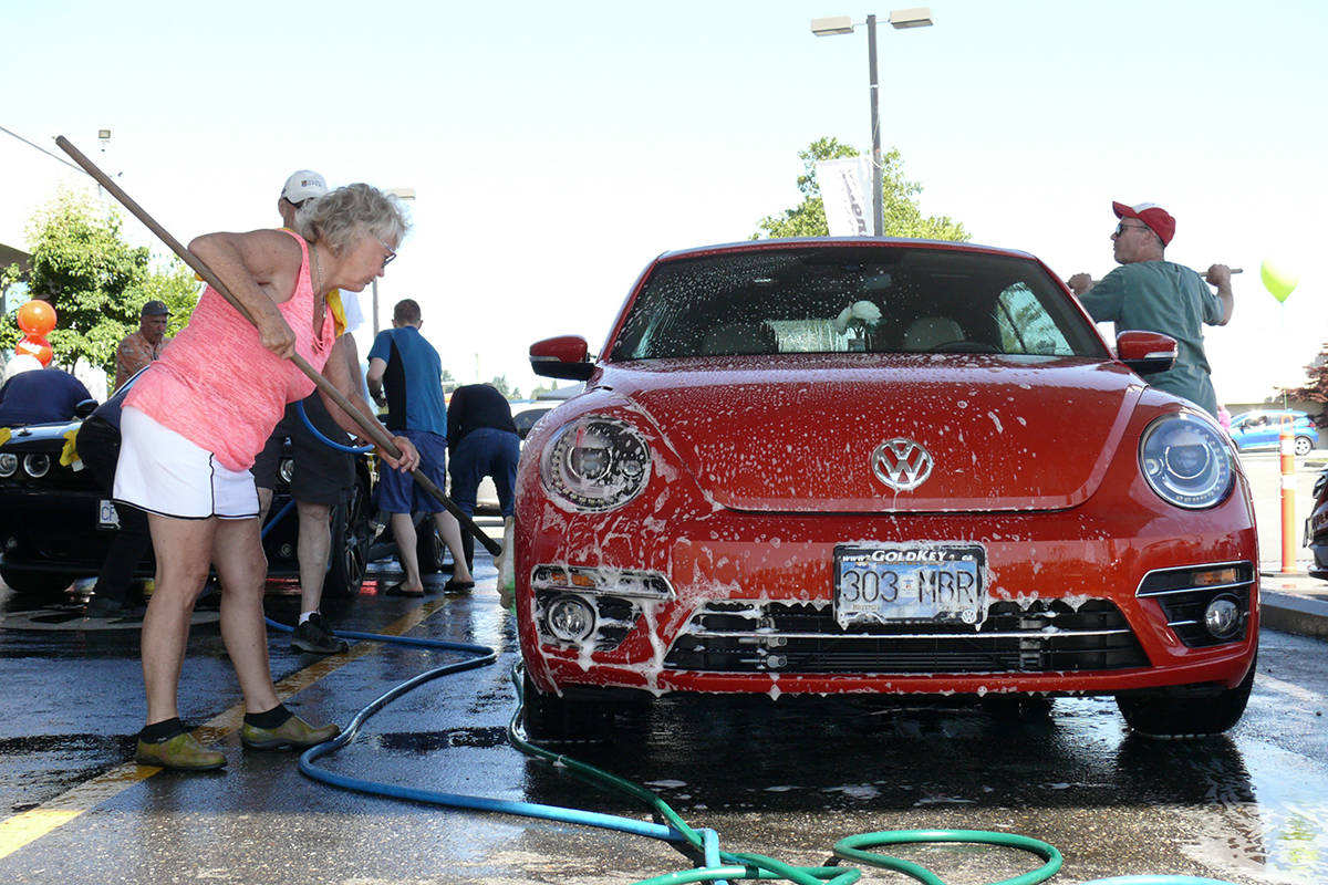 Walnut Grove resident Beverly Genge applies soap to Langley City mayor Val van den Broek's car. Genge has been volunteering with the cancer drivers for three years. (Dan Ferguson/Langley Advance Times)
