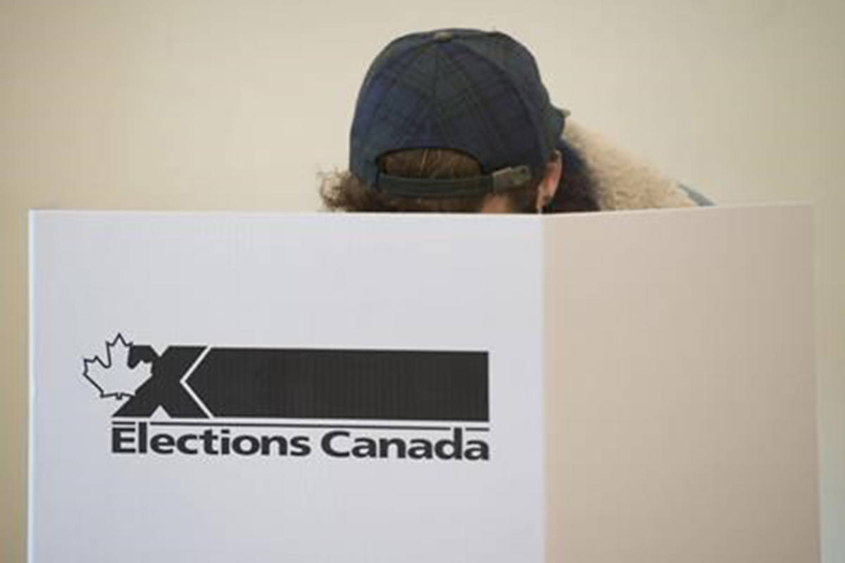 A woman marks her ballot behind a privacy barrier in the riding of Vaudreuil-Soulanges, west of Montreal, on October 19, 2015. A Federal Court judge is ordering the chief electoral officer to take a second look at whether voting day this October needs to be moved because it falls on a Jewish holiday. THE CANADIAN PRESS IMAGES/Graham Hughes