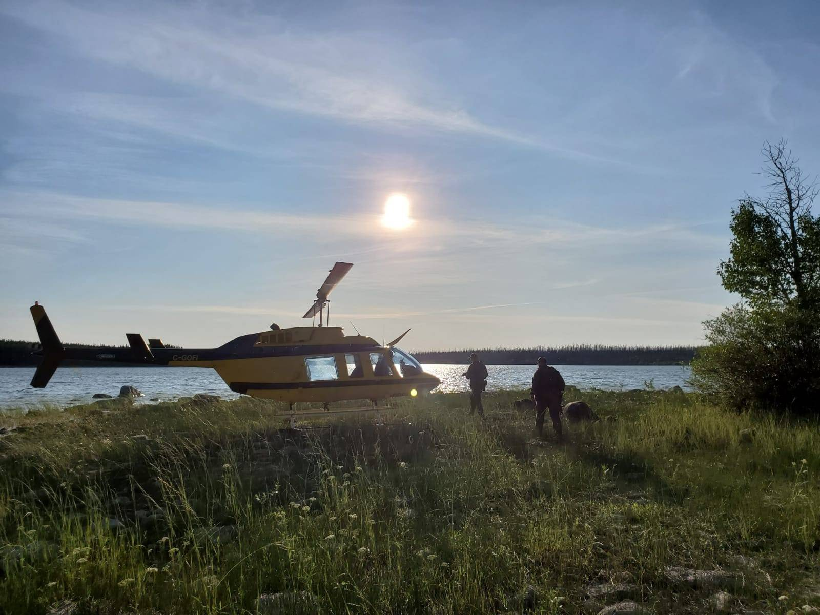 Officers look through a remote lake area alongside a landed helicopter in the Gillam, Man., area in July 28, 2019, police image published to social media. (Royal Canadian Mounted Police photo)