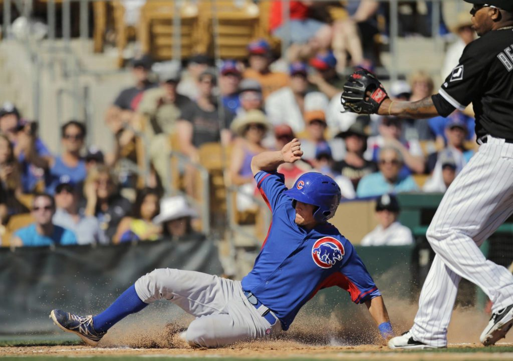 Chicago Cubs' Wes Darvill slides home to score from third on a wild pitch by Chicago White Sox reliever Ronald Belisario, right, in the seventh inning of a spring exhibition baseball game Friday, March 21, 2014, in Glendale, Ariz. (AP Photo/Mark Duncan)