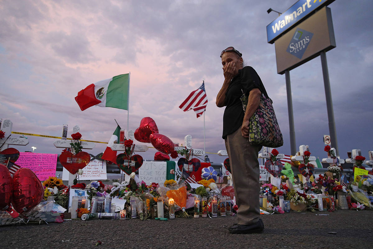 Catalina Saenz wipes tears from her face as she visits a makeshift memorial near the scene of a mass shooting at a shopping complex Tuesday, Aug. 6, 2019, in El Paso, Texas. A list of the people who died in the weekend shooting rampage at the Walmart, shows that most of the victims had Latino surnames and included one German national. (AP Photo/John Locher)