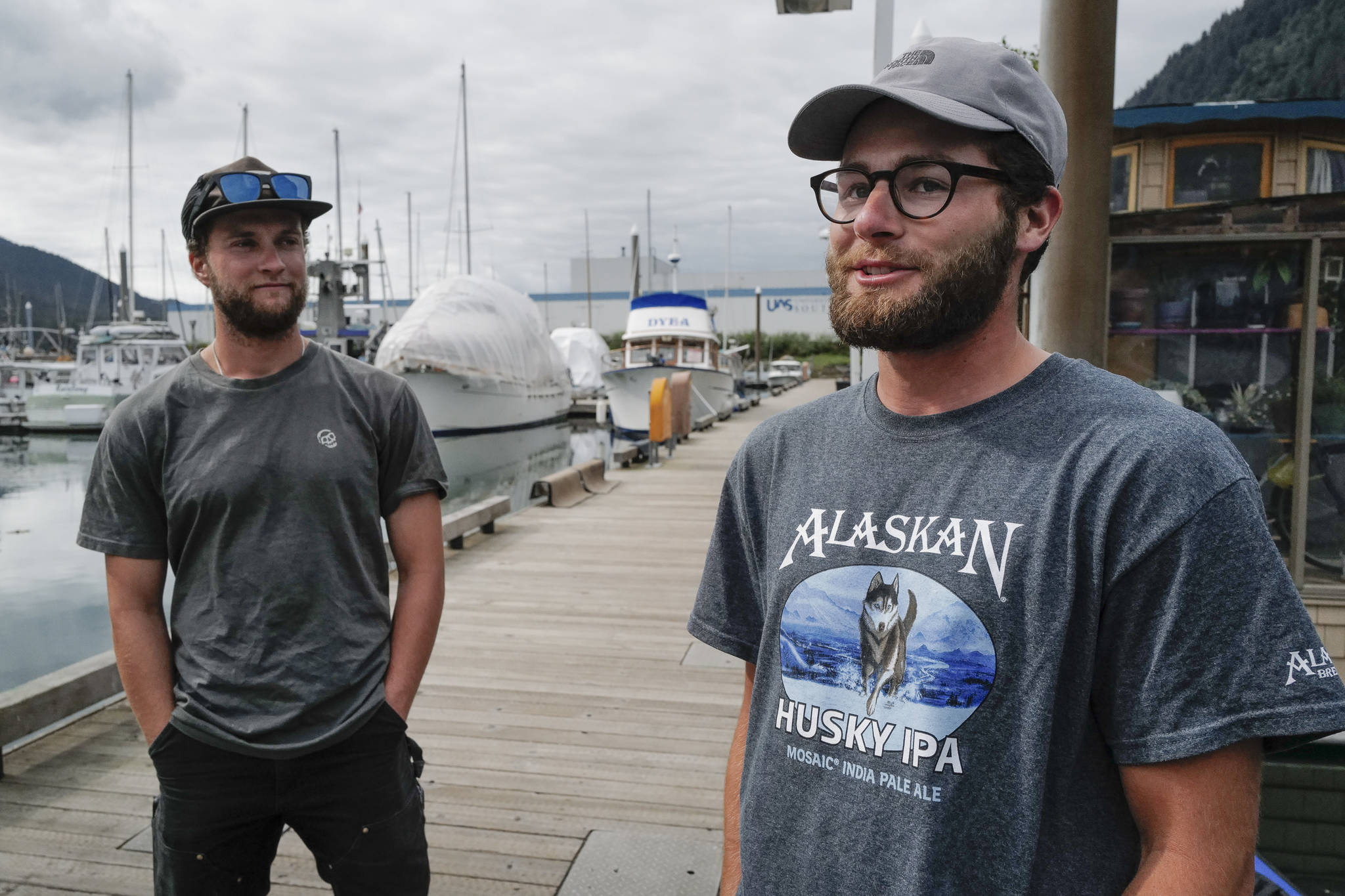 Liam Godfrey-Jolicoeur, left, and Jake Dombek, talk at Harris Harbor on Thursday, Aug. 2, 2019, about their nearly two-month long trip up the Inside Passage by canoe. Both are orginally from Vermont used the trip to raise money and bring awareness to environmental causes. (Michael Penn | Juneau Empire)