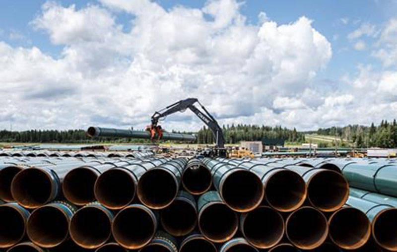 Pipe for the Trans Mountain pipeline is unloaded in Edson, Alta. on Tuesday June 18, 2019. (THE CANADIAN PRESS/Jason Franson)