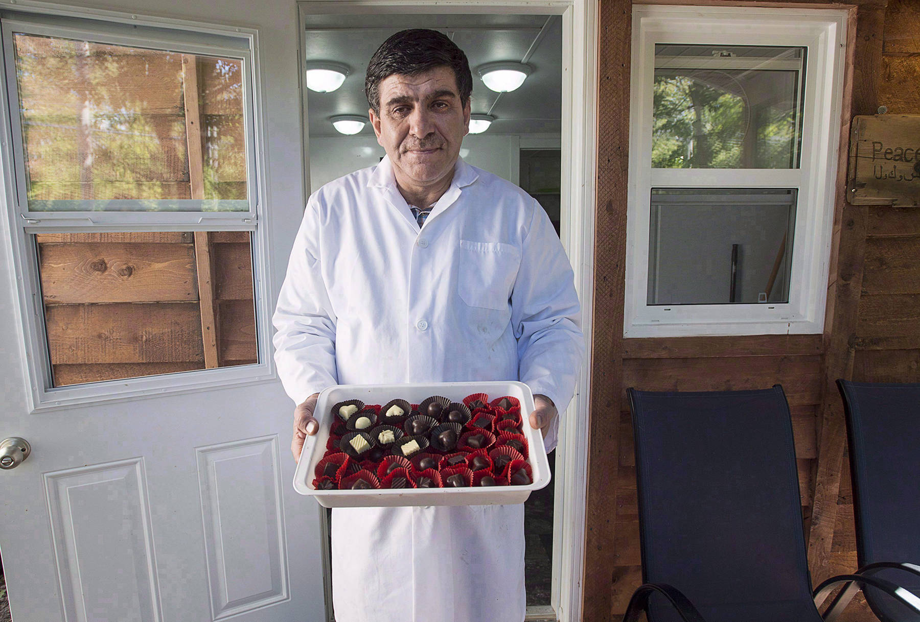 Assam Hadhad, a Syrian refugee who arrived in Canada last year, displays a tray of chocolates at his shop, Peace by Chocolate, in Antigonish, N.S. on Wednesday, Sept. 21, 2016. CEO Tareq Hadhad has plans to hiring more refugees over the next three years. (Andrew Vaughan/The Canadian Press)